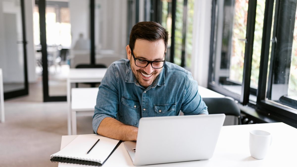 cheerful businessman using laptop bright office space